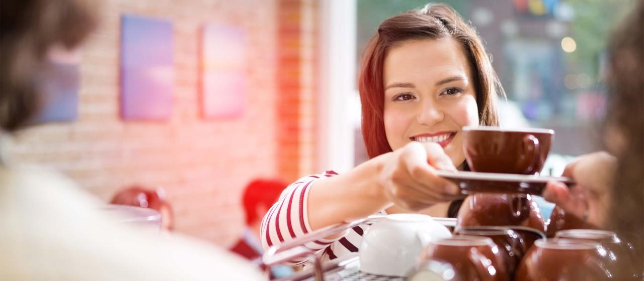 Junge Frau reicht Kaffeetasse über den Tresen